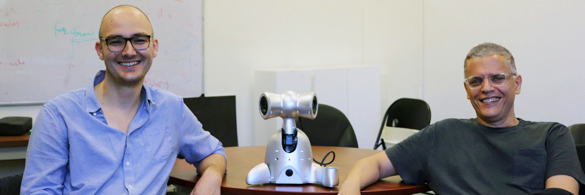 Ph.D candidate Richard Savery and Professor Gil Weinberg pose with a Shimi, one of the robots from the Robotic Musicianship lab.