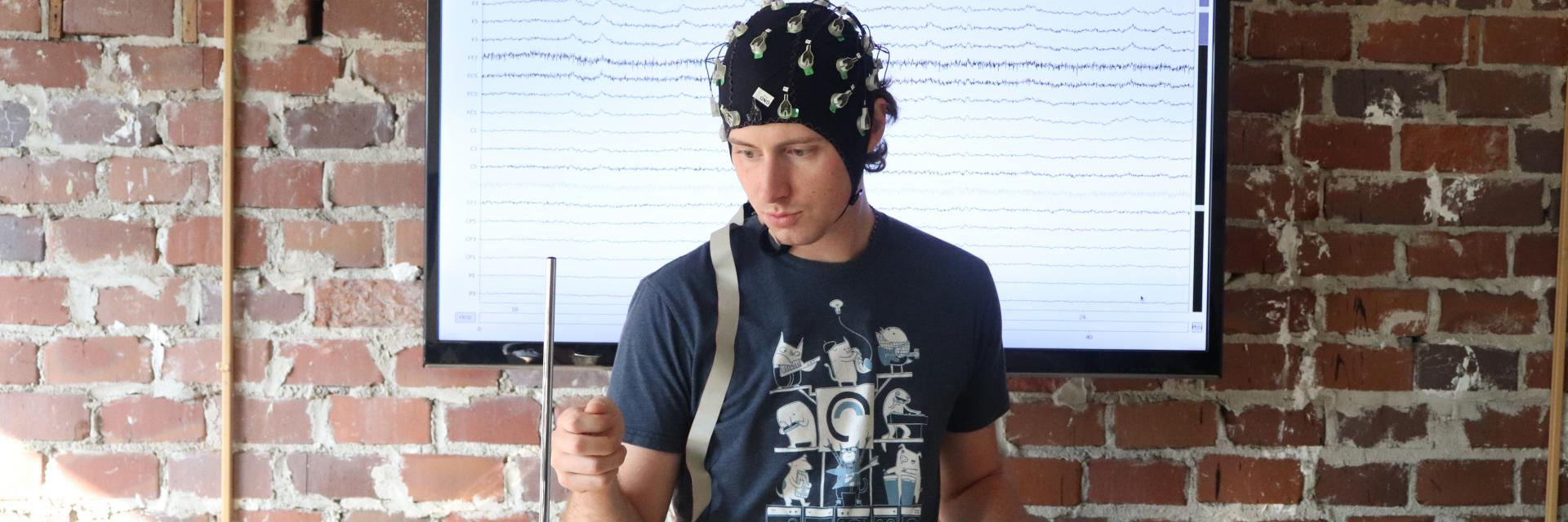 Mike Winters, a Ph.D. student, playing a theramin while wearing a brain scan cap.