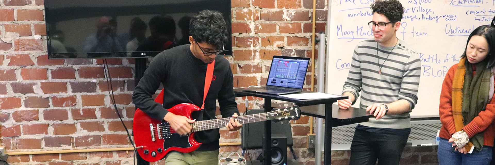 A student plays the guitar as part of a project presentation.