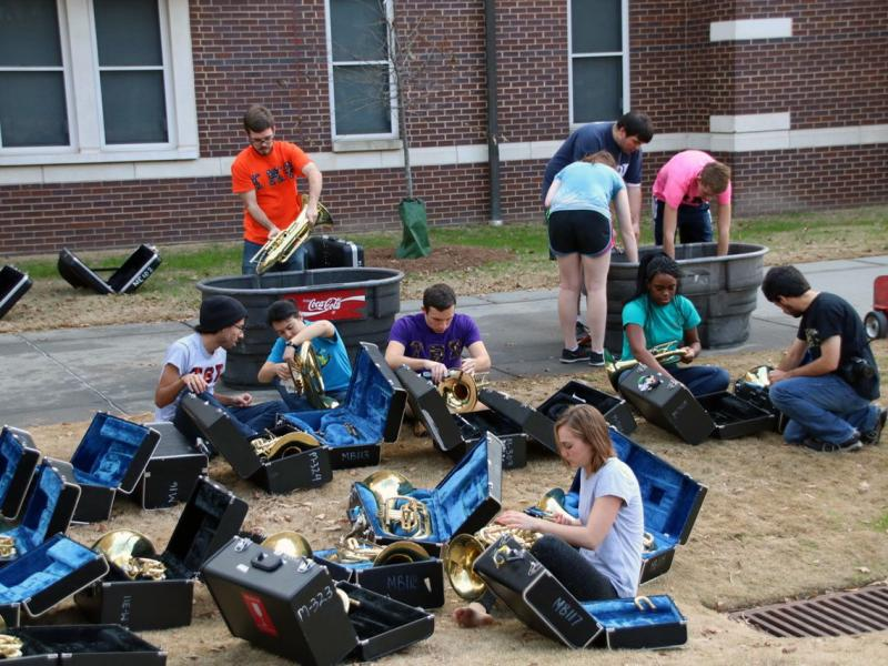 A group of students working on repairing brass instruments outside on the Couch building lawn.