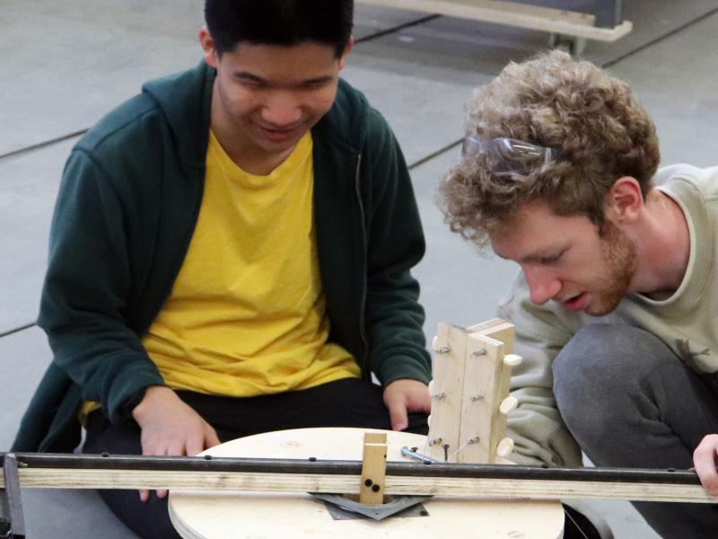 Two students working on part of a musical Rube Goldberg machine.