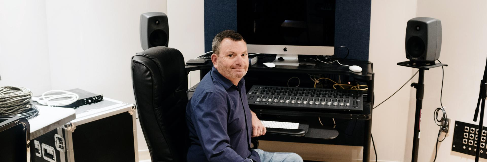 Chris Moore sitting in the School of Music's MIDI studio.