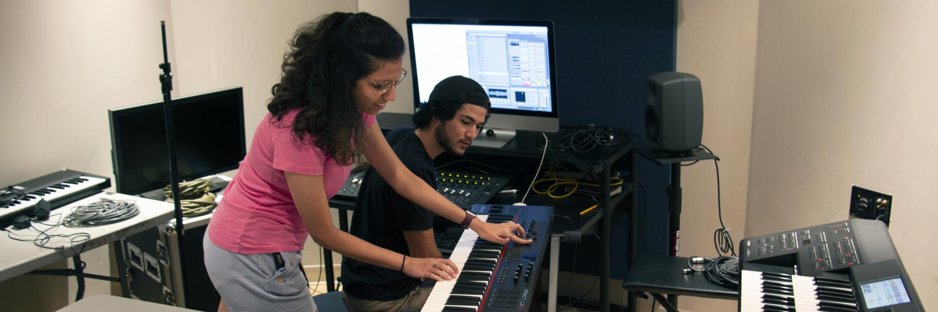 A female student plays the keyboard while a male student watches to record her in a studio.