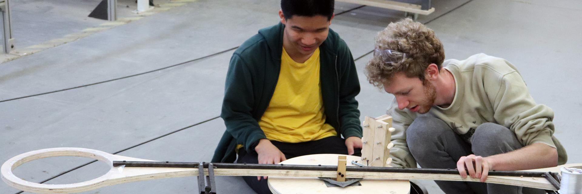 Two Undergrad students working on a Rube Goldberg machine at the Digital Fabrication Lab.
