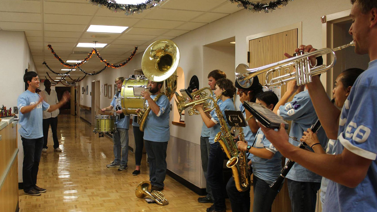 Members of the Kappa Kappa Psi marching band fraternity play in a hospital hallway, decorated with festive garlands.