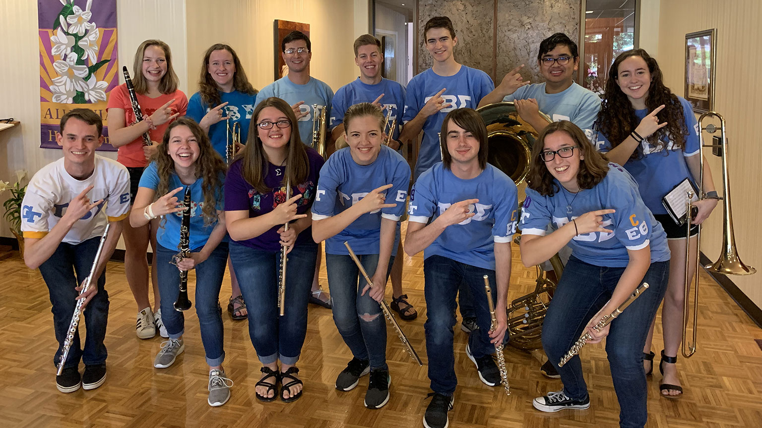 A group of Tau Beta Sigma sorority members pose with their instruments for a group photo. All the people in this photo are wearing shirts with the Greek letters for Tau Beta Sigma on them.
