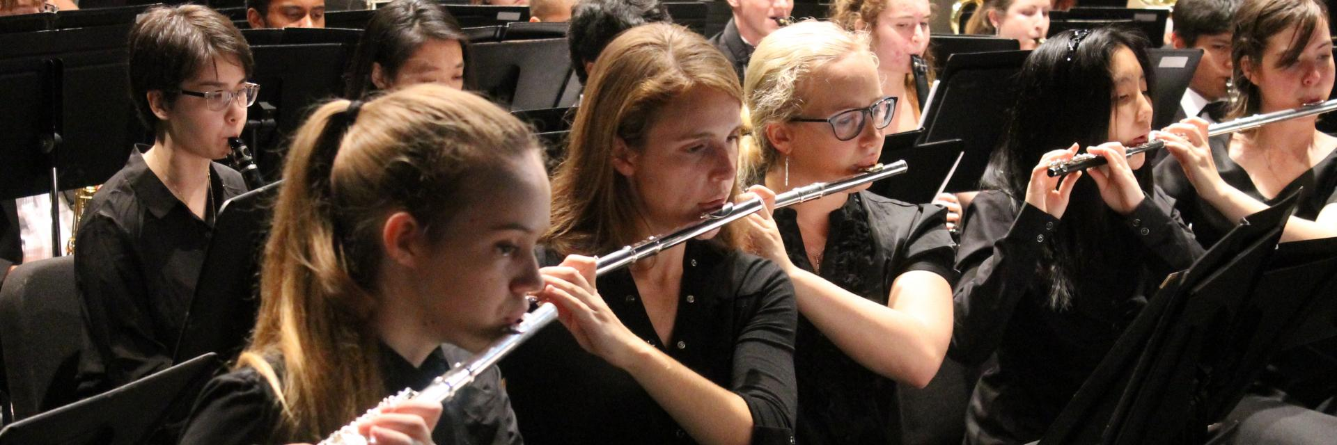 Students in the band playing on their flutes during a concert.