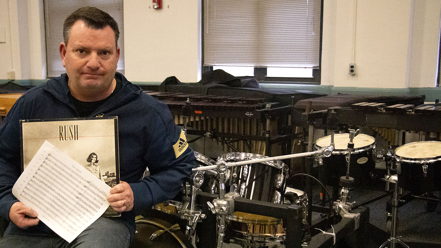 Chris Moore sits in the band room at Georgia Tech holding the sheet music to Tom Sawyer and his vinyl album of Rush's Permanent Waves.