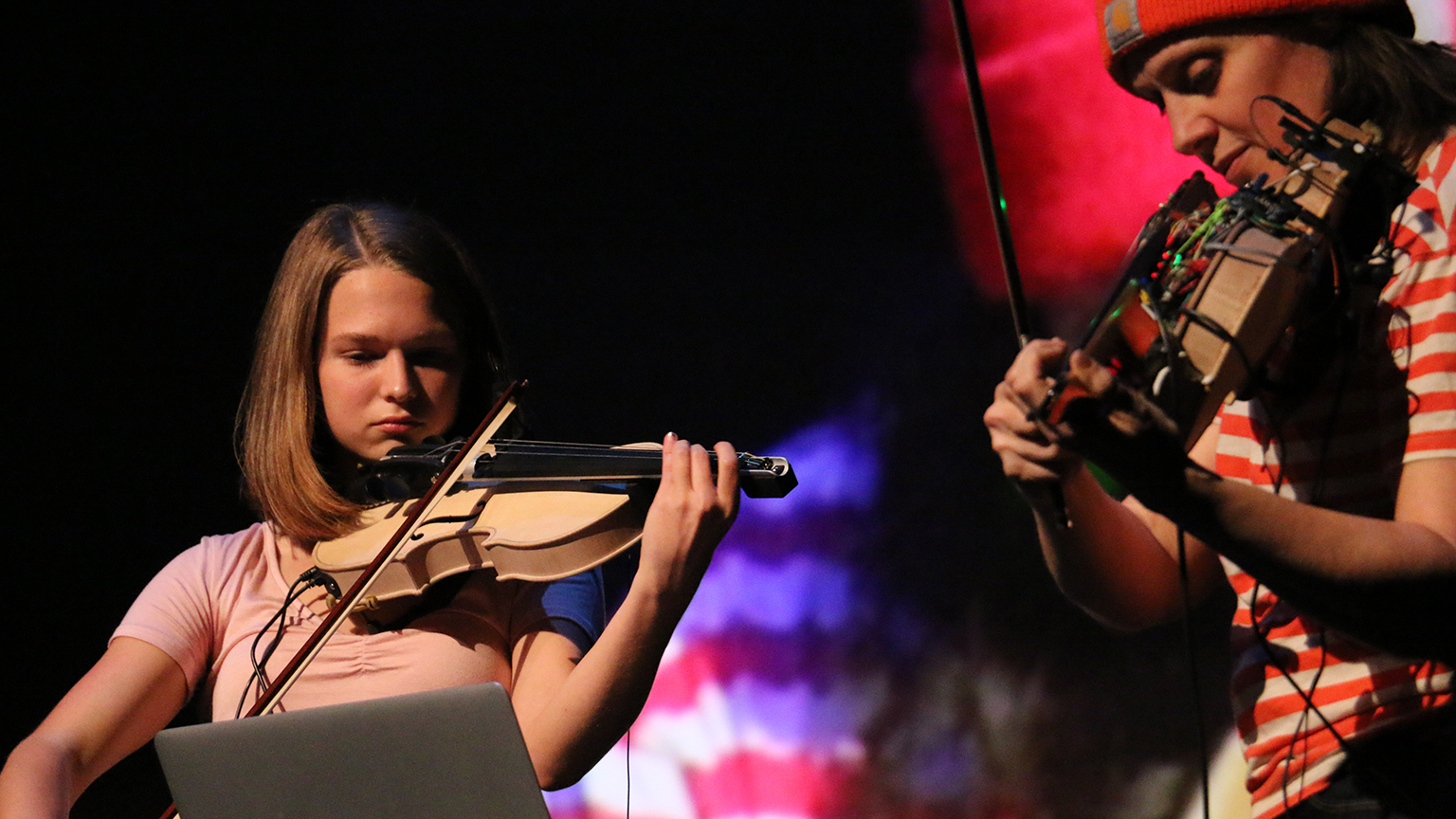 A student playing a violin in concert next to a creator with a modified violin.