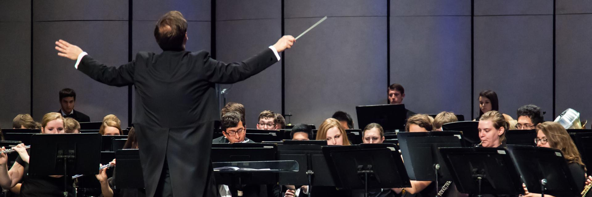 The Symphonic Band conductor directing students at a band concert.