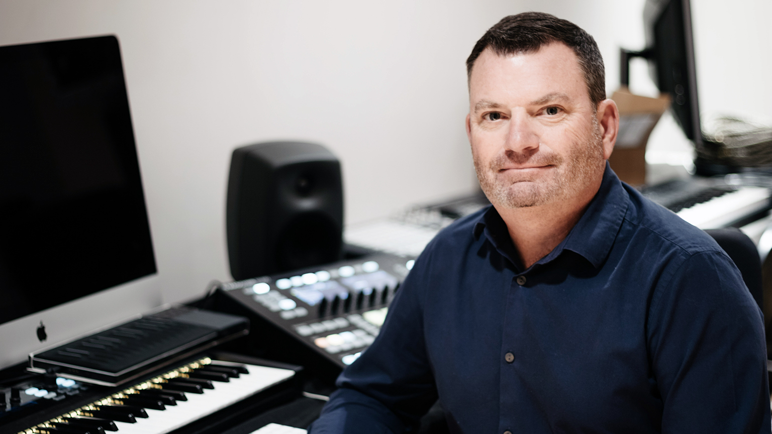 Chris Moore smiling next to a computer and electronic piano.