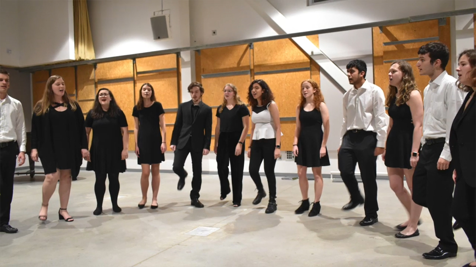 A group of choral students dressed in black and white performing in a concert in the West Village.