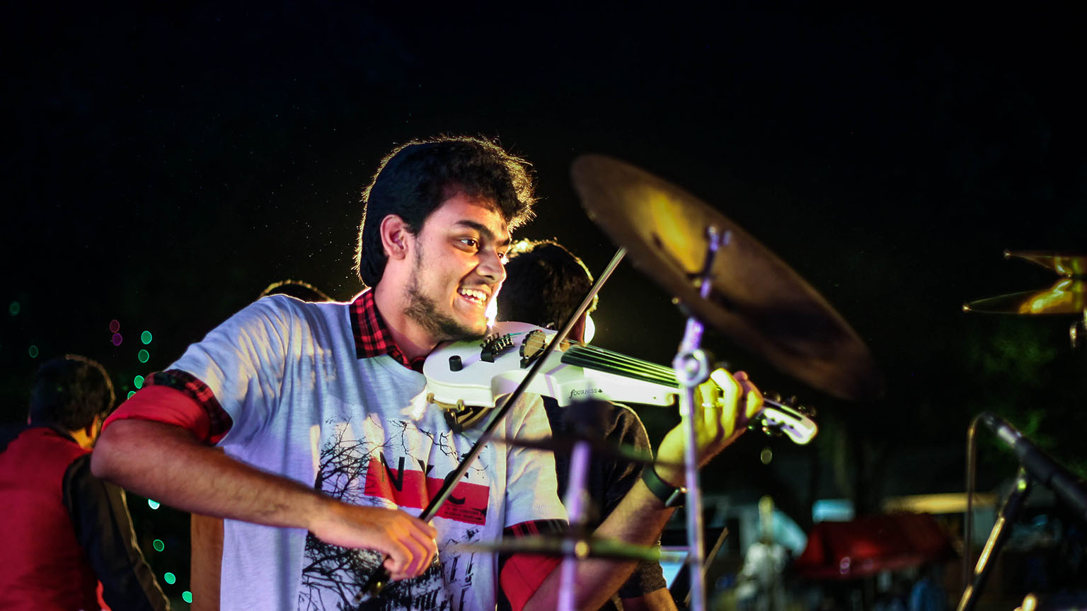 Raghav playing a white violin in a performance on stage.