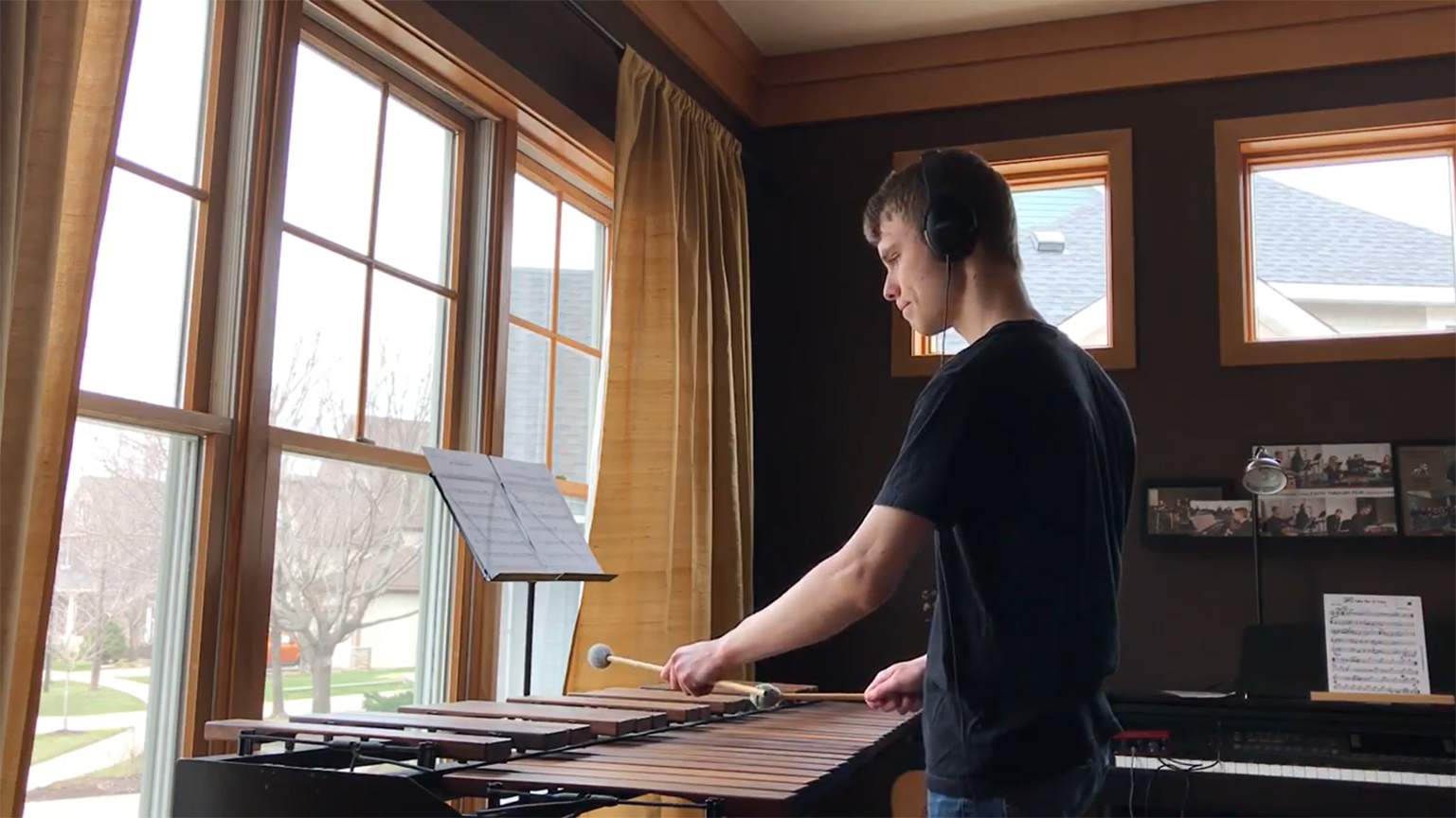 A student playing a marimba while looking at sheet music.