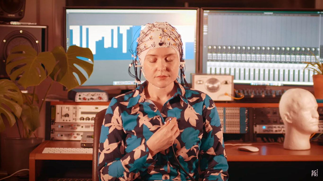 Grace Leslie wearing a cap with wires designed to measure brain waves, while sitting in front of a small studio console.