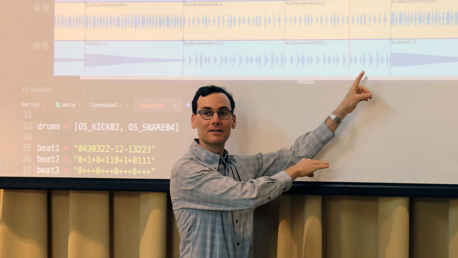 Jason Freeman teaching in front of a projector screen showing lines of code.