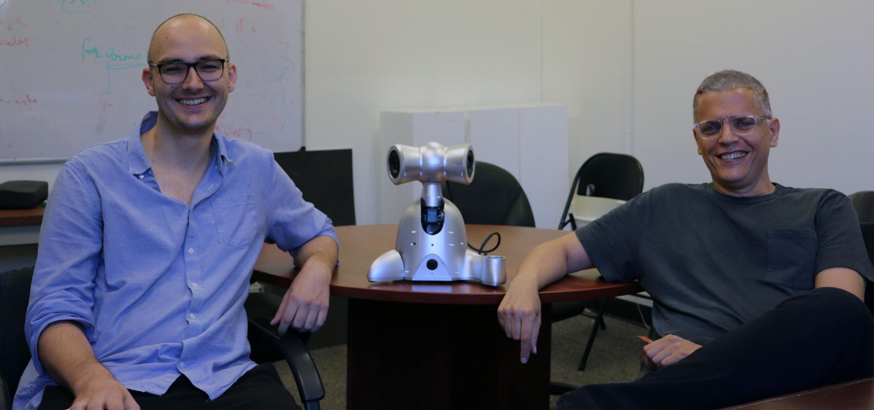 Gil Weinberg and Richard Savery pose with a Shimi robot, one of the robots created by the Robotic Musicianship group.